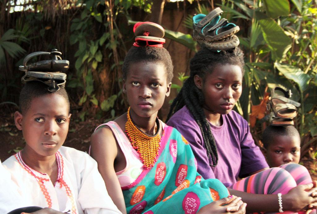 """Vier Mitglieder der Sosolyas während der Theaterproben zu """"Zakayo"""" in Uganda. Sie tragen ihre Kostüme, wobei sie alte Sandalen auf dem Kopf tragen."""